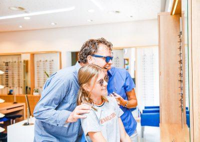 Mit einer Brille von Hirt sehen sich Menschen glücklich im Spiegel